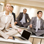Portrait of meditating partners sitting on desks with their legs crossed in office